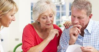 Older-couple-with-adviser-looking-at-document-kitchen_320x170